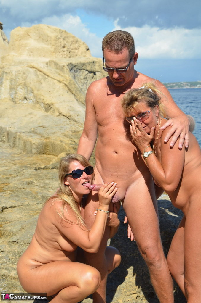 Nudist gets his cock sucked by two women on the beach