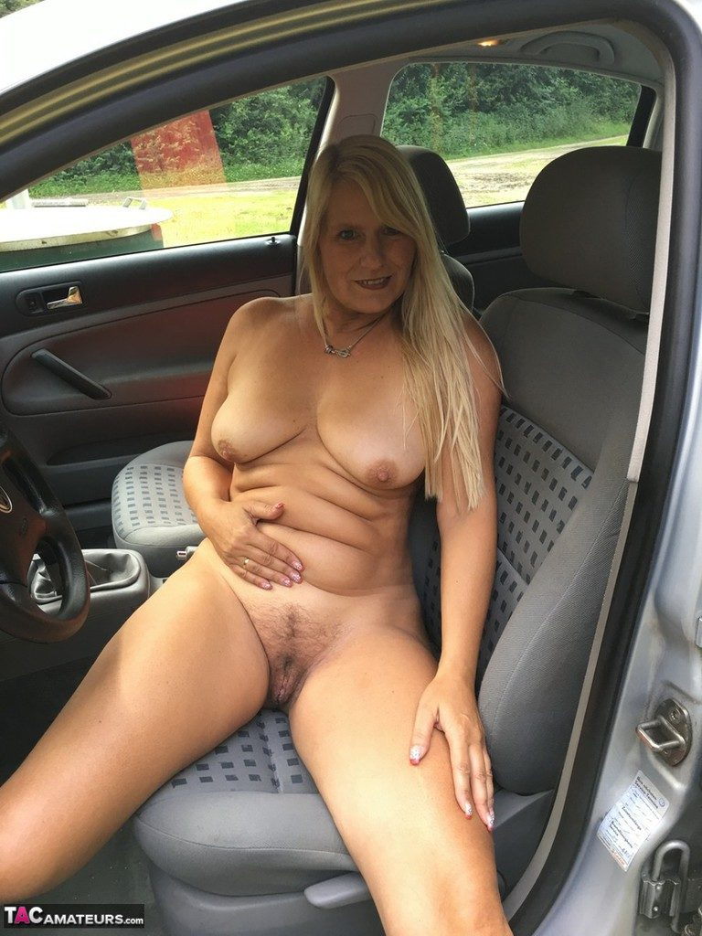 Car exhibitionist with a big belly flashes her hairy cunt to strangers